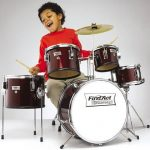 a kid playing on a five piece set