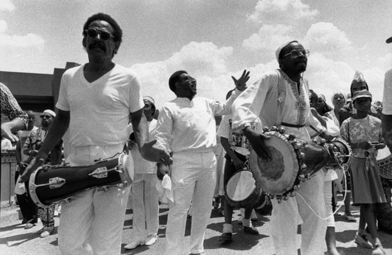 black and white photo on which people are playing bata drums and dancing