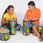Four kids sitting on the floor and playing Remo floor drums