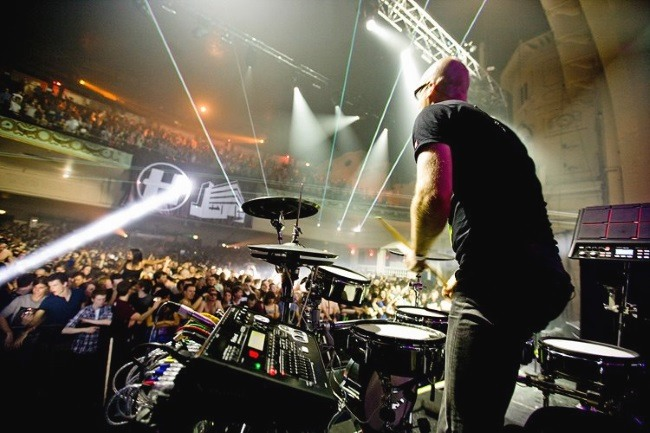 a drummer playing electronic drum pads on the stage in front of a crowd